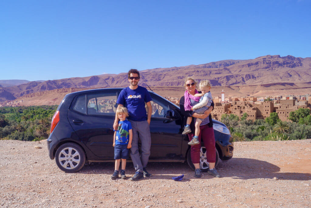 family stood by car in Morocco