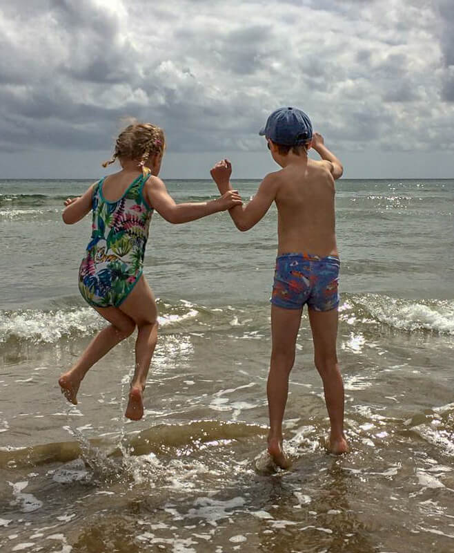 boy and girl jumping in waves
