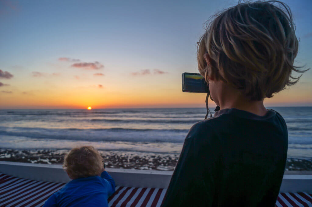 two boys taking a photo of the sunset