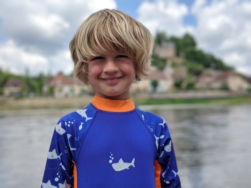 boy by river in wetsuit