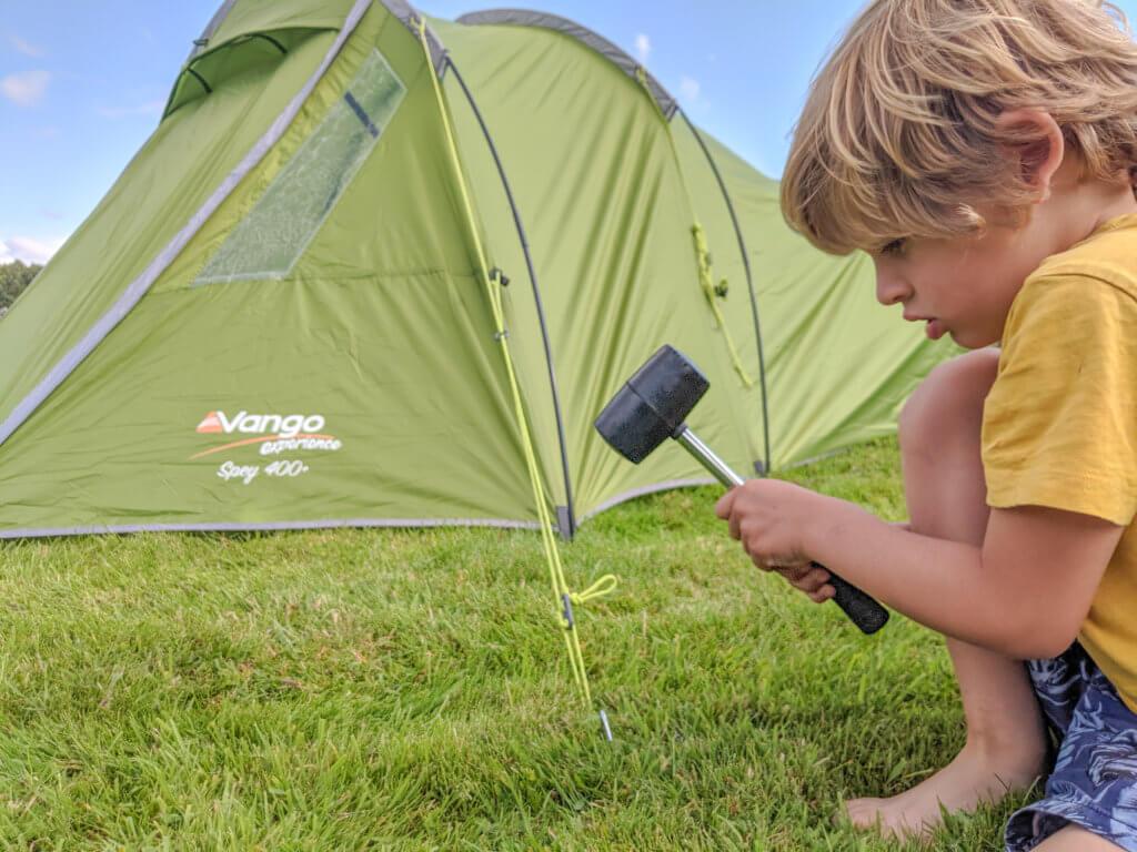 boy hammering tent pegs in
