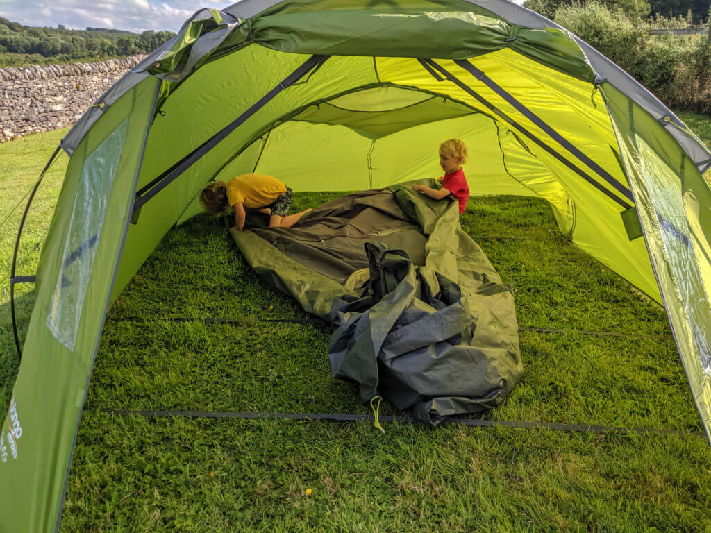two boys putting tent up