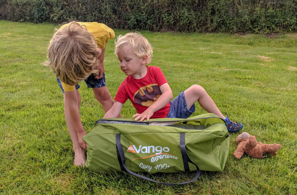 two boys opening tent bag