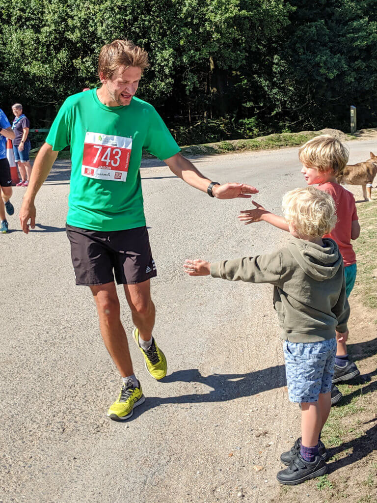 man running and high fiving kids